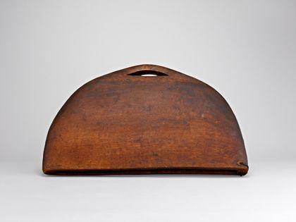 Ganz flache, im Umriss fast halbkreisförmige Holzpauke aus einem Stück Holz gefertigt. Von unten her ist das Instrument ausgehöhlt. Oben befindet sich eine Durchbohrung als Handgriff. Der Schlägel aus Holz hat eine verharzte Wicklung aus Bast, mit der die Pauke geschlagen wurde.