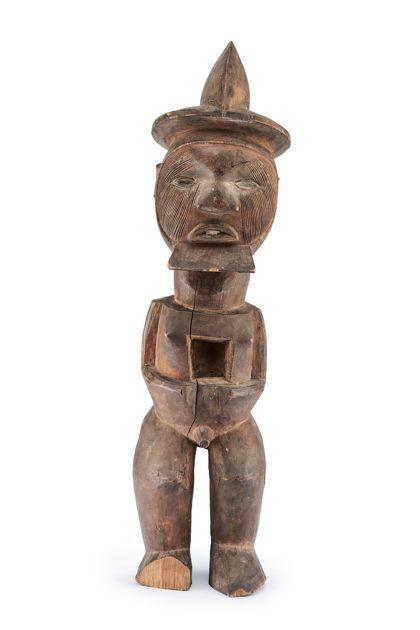 Männliche Figur aus Holz, mit helmartiger Kopfbedeckung und viereckigem Bart, im Bauch eine viereckige Aussparung.