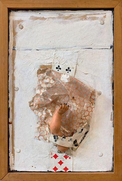 Assemblage aus Spielkarten, Puppenarm und anderen Materialien auf weiß bemaltem Bildträger