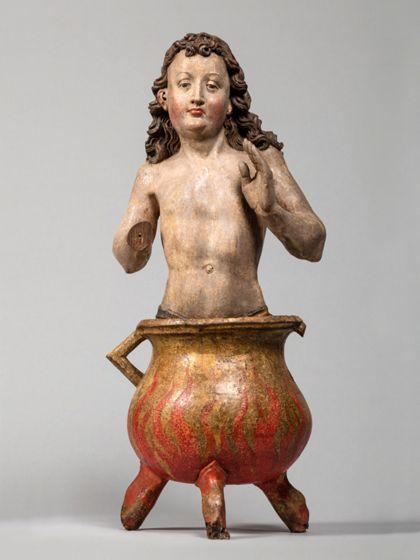 Holzskulptur des heiligen Vitus, der in Halbfigur nackt in einem Kessel sitzt.