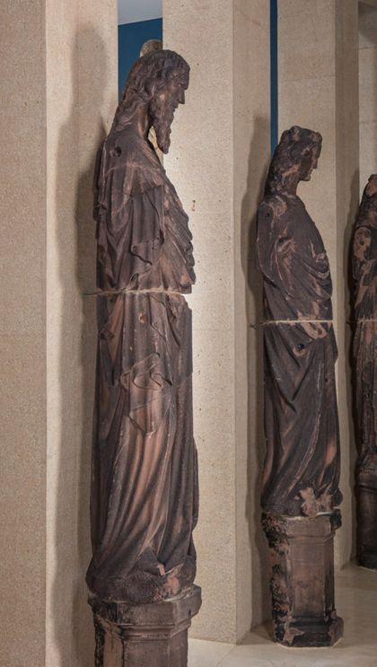 Weit überlebensgroße Sandsteinfigur eines schmalen, in den Proportionen gelängten Propheten ohne Attribute, Seitenansicht von links.