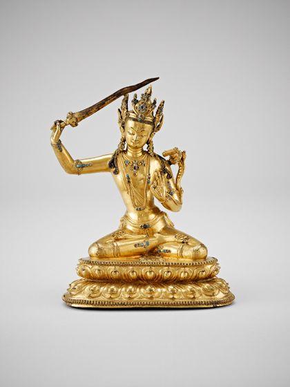 Reich mit Schmuck verzierte Figur des Manjushri, aus vergoldeter Bronze, sitzend auf plastisch verziertem Sockel in abgerundeter Dreiecksform. Die rechte Hand hält das Schwert über den Kopf.