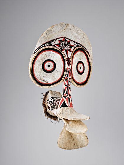 Eine große, sehr plastisch aus Bambus und hellem Rindenbaststoff gefertigte Maske, die durch ihre Form wie die rote und schwarze Bemalung ein stilisiertes, animalisches Gesicht mit großen Augen und einem schnabelartigem Mund zeigt.