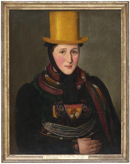 Portrait einer Frau in Tracht, mit gelbem Zylinder. Golden gerahmt.