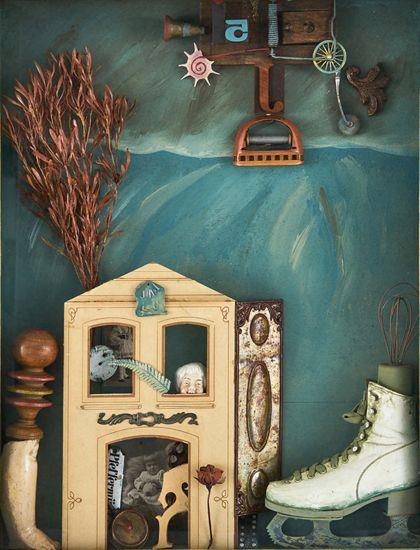 Objektkasten mit Schlittschuh, Haus, Puppenbein und anderem vor hellblauem Hintergrund