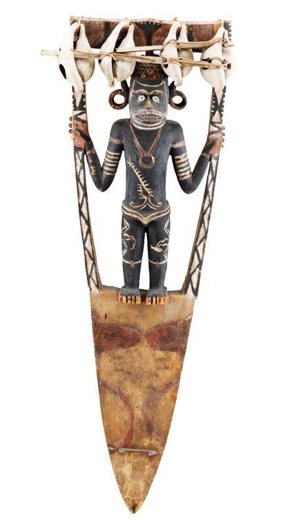 Menschliche Figur in einem Rahmen stehend, den sie mit beiden Händen hält. Nach unten bildet der Rahmen ein Sockelbrett, das spitz zuläuft.