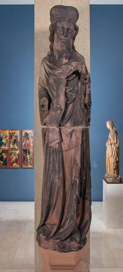 Weit überlebensgroße Sandsteinfigur eines schmalen, in den Proportionen gelängten Propheten mit mit Kappe und Schriftband.