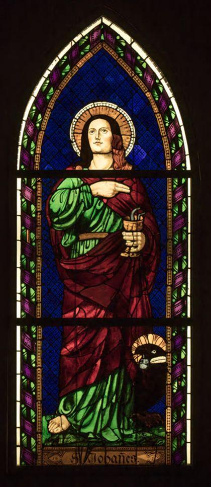 Spitzbogiges Kirchenfenster mit der Darstellung des stehenden Johannes Evangelist.