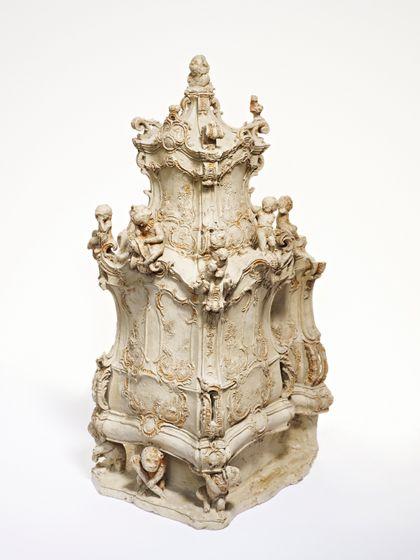 Barock verziertes Ofenmodell mit zahlreichen Voluten und Putten
