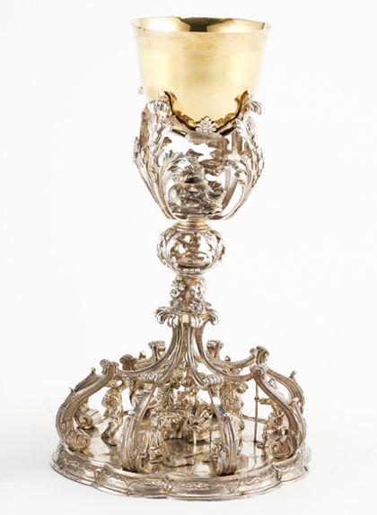 Der silberne Kelch mit vergoldeter Kuppa besitzt filgrane Durchbrüche, in denen kleinteiliger Figurenschmuck eingestellt ist, im Fußbereich die Geburt Christi.