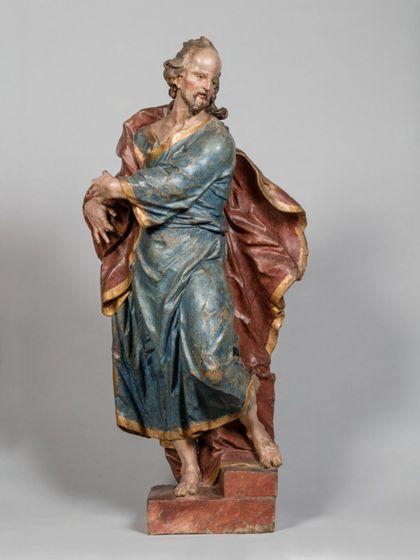 Stehende Holzskulptur des Apostels Judas Thaddäus in theatralisch verdrehter Körperhaltung und ebenso expressiver Drapierung des stoffreichen Gewands.