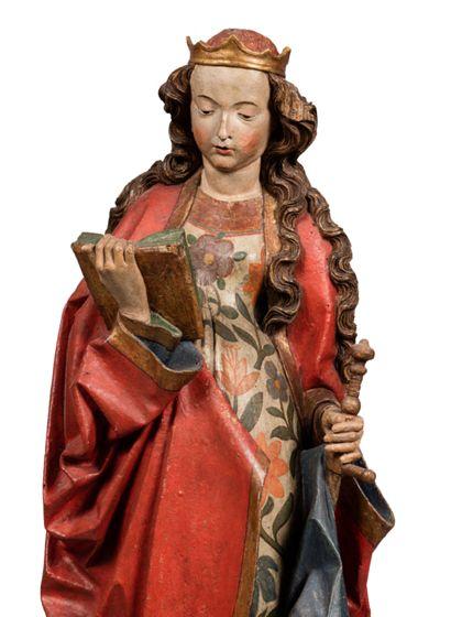 Die gefasste Holzskulptur der heiligen Katharina in langer, vorne geraffter Gewandung hält in der rechten ein Buch, in der Linken ein Schwert, Detail des Oberkörpers.