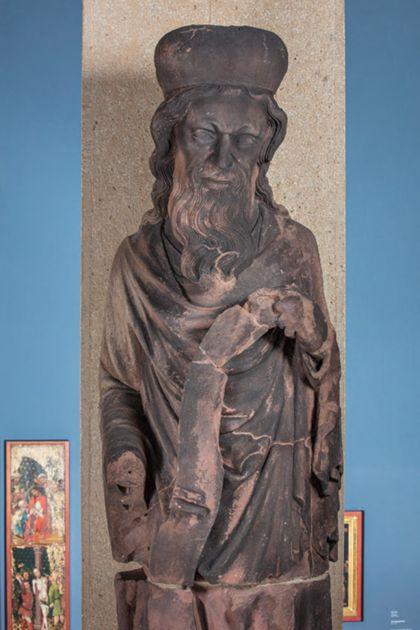 Weit überlebensgroße Sandsteinfigur eines schmalen, in den Proportionen gelängten Propheten mit mit Kappe und Schriftband, Detail des Oberkörpers.