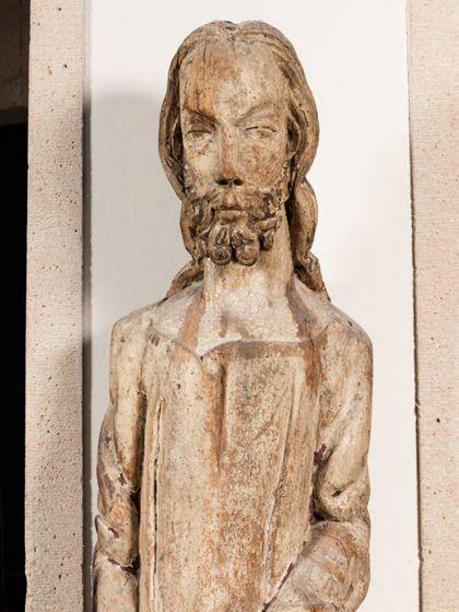 Überlebensgroße, sehr schmale Holzskulptur einer männlichen Gestalt mit extrem gelängten Proportionen, Detail des Kopfes und des Oberkörpers.