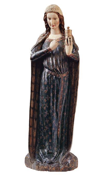 Ganzfigurige Holzskulptur der heiligen Maria Magdalena in langem Gewand und langem Umgang. Mit der linken präsentiert sie das Salbgeföäß. Die rechte Hand greift zum Mantelverschluß.