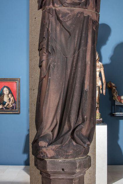 Weit überlebensgroße Sandsteinfigur eines schmalen, in den Proportionen gelängten Propheten ohne Attribute, Deatil der unteren Partie der Skulptur.