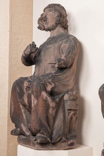 Sandsteinfigur eines sitzenden Grafen mit Blütenkranz, Seitenansicht von rechts.
