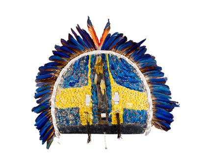 Große Gesichtsmaske in Form eines Halbkreises, deren Vorderseite mit blauen und gelben Arara-Federn beklebt ist. Die Durchbrüche für Augen und Mund sind mit Perlmutt-Einlagen geschmückt.