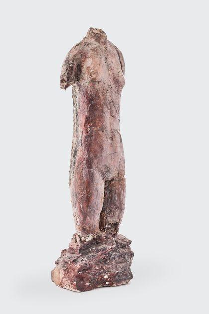 Weiblicher Bronzetorso auf einem Sockel stehend