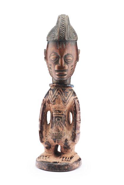 Aus einem Stück rötlichbraunem Holz geschnitzte Ibedji-Figur, die zudem mit rötlichem Ton eingerieben wurde. Die helmartige Kopfbedeckung ist reich mit Kerbschnittmuster (Gitterschnitt in geometrischen Feldern) verziert. Am Körper, an den Armen, auf der Stirn und auf den Wangen befinden sich kurze eingeschnitzte Schmucknarben. Um den Hals trägt die Figur eine Halskette.