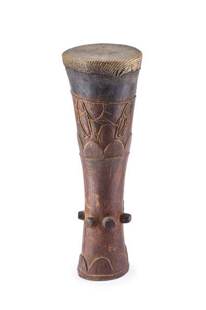 Eine sanduhrförmige Kriegstrommel, die mit Schlangenhaut bespannt und mit geschnitztem Ornament verziert ist.