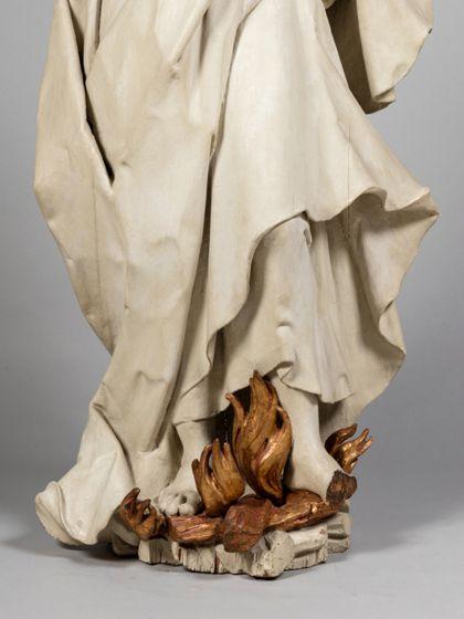 Monochrom hell gefasste Holzskulptur der heiligen Afra, die in lodernden Flammen steht, Detail der unteren Gewandpartie.