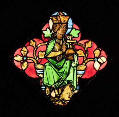 Kirchenfenster mit der Darstellung einer thronenden weiblichen Heiligen vor rotem Grund.