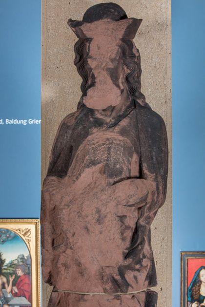 Stark beschädigte, überlebensgroße Sandsteinfigur eines schmalen, in den Proportionen gelängten Propheten mit Kappe, Detail des Oberkörpers.