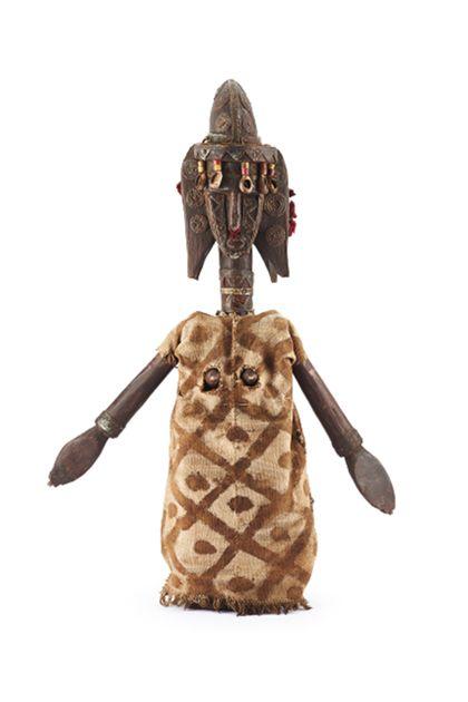 Die Figur weist einen reduzierten, blockhaften Korpus auf, der hinten ausgehöhlt ist und aus hartem Holz gefertigt wurde. Die Arme sind aus leichterem Holz gearbeitet und wurden in seitliche Aussparungen eingelassen und mit Eisennägeln befestigt. Die konischen Brüste sind relativ tief angesetzt. Der Hals ist lang, darüber ein schmales Gesicht mit ausladender Frisur. Über der runden Stirn befindet sich ein breiter Steg unter dem die lange, schmale, gerade Nase folgt. Die Frisur am Oberkopf ist sehr hoch aufgetürmt. Die Figur ist insgesammt stark verziert: Kupfer- bzw. Messingblechstreifen und -scheiben, mit eingestanzten Punktreihen und Zickzacklinien zieren das Gesicht, die Frisur, den Hals und die Handgelenke. In der Nase und in je drei Löchern in den Ohren sind Bommel aus roten Baumwollfäden angebracht. Vom Steg über der Stirn hängen fünf Kaurischnecken an mit je zwei gelb-roten Glasperlen verzierten Schnüren. Der Korpus ist bekleidet mit einem Kleid aus handgewebtem Baumwollstoff, das verziert ist mit braunem Rauten- und Punktmuster in Flafanitechnik (Pflanzensud und Schlammbad); im gerade geschnittenen Kleid sind zwei Löcher für die Brüste eingeschnitten.