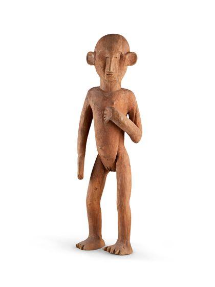 Weibliche Figur aus leichtem Holz geschnitzt mit Rötel gefärbt. Der rechte Arm hängend, die linke Hand befindet sich vor der Brust. Die Ohren sitzen sehr weit vorne.