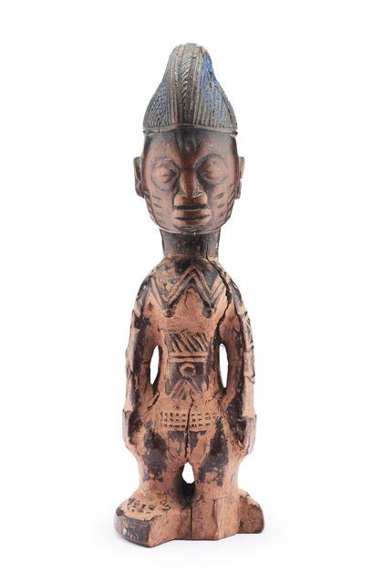 Aus einem Stück rötlichbraunem Holz geschnitzte Ibedji-Figur, die zudem mit rötlichem Ton eingerieben wurde. Die helmartige Kopfbedeckung ist reich mit Kerbschnittmuster (Gitterschnitt in geometrischen Feldern) verziert. Am Körper, an den Armen, auf der Stirn und auf den Wangen befinden sich kurze eingeschnitzte Schmucknarben. Aus dem Sockel ist ein Stück ausgebrochen.