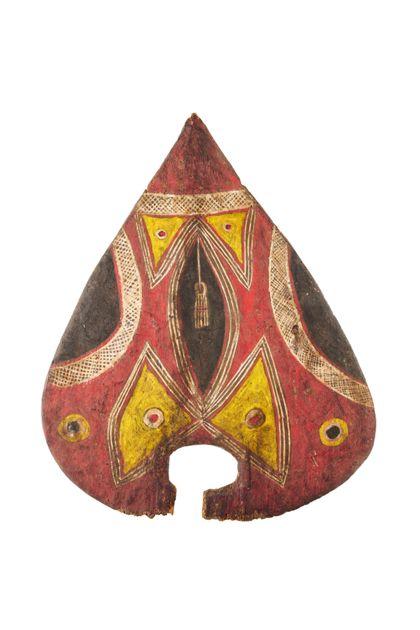 Kleiner, herzförmiger Tanzschild aus leichtem Holz und bemalt mit geometrischen Figuren in gelb, schwarz und weiß auf rotem Grund. Oben eine ovale Durchbohrung.