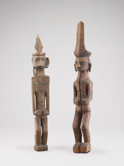 Die längliche Holzfigur zeigt eine Vertreterin der Oberschicht. Sie trägt eine hohe Krone und schweren Goldschmuck, der die Läppchen lang zieht. Durch Einkerbungen nahe dem Hals ist der breite goldene Halsschmuck erkenntlich.