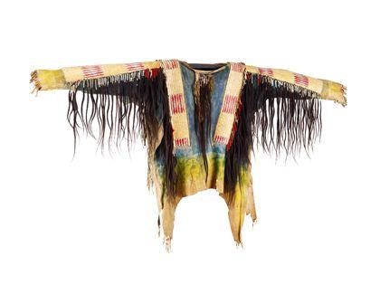 Ein Hemd aus Hirschleder, das teils blau gefärbt und mit breit breiten Lederstreifen verziert ist, die an den Kanten mit Skalphaaren besetzt sind.