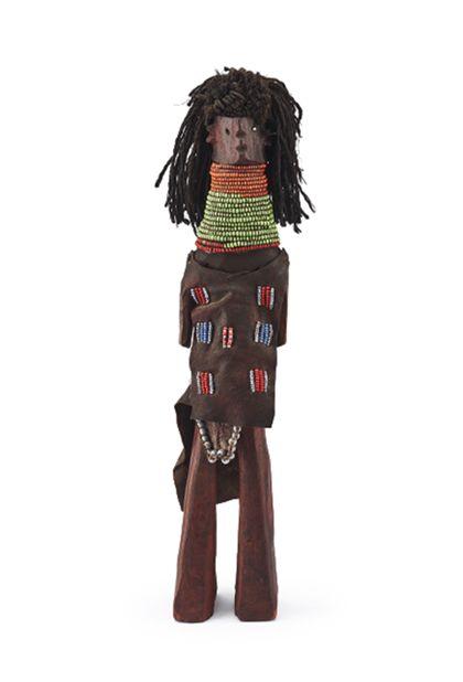 Rotbraun eingefärbet Holzpuppe. Die Beine der Puppe verdicken sich nach unten hin, so dass sie stehen kann. Die Hände und Füße sind nicht ausgearbeitet. Mund und Nase werden mittels Einkerbungen dargestellt. Die Ohren heben sich seitlich vom Kopf ab. Die Frisur ist aus dunkelbraun eingefärbten Schnüren gefertigt, vorne kurz abgeschnitten, hinten lang. Die Puppe trägt einen Brust-, Schoß- und Gesäßschurz, alle aus Leder mit bunten Perlen verziert oder mit größeren Perlen eingefaßt. Um den Hals und Nacken trägt die Puppe ein breites Band aus vielen Perlenreihen in orange, grün und rot.