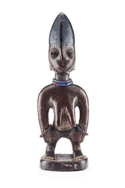 Ibeji Figur mit hoher Frisur, die mit Kerbschnitten versehen und dunkelblau bemalt ist. Die vorstehenden Augen weisen Löcher für die Pupillen auf. Im linken Auge befindet sich ein Metallpfropf. Die Ohren sind weit nach hinten gerückt. Über den Schläfen und den Wangen sind vertikale, zum Kinn horizontale Schmucknarben eingeschnitzt. Die Figur trägt eine blaue und rote Kette um den Hals, eine schwarze Kette um den Leib und an beiden Armen eine blaue Perlenkette.