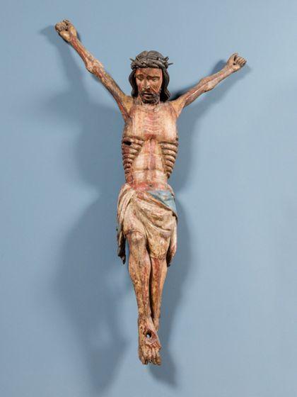 Die Holzfigur mit resten alter Fassung zeigt den Gekreuzigten mit weit nach oben gestreckten Armen. Das Gabelkreuz ist nicht erhalten.