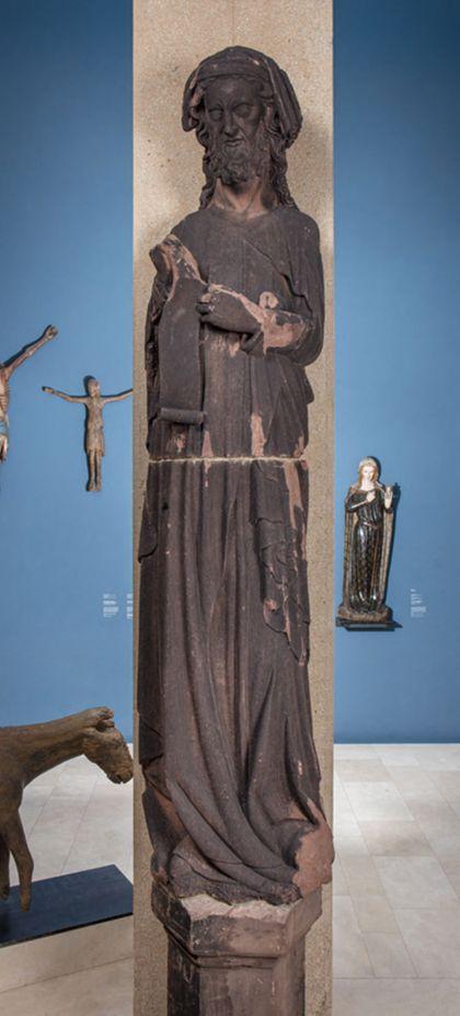 Weit überlebensgroße Sandsteinfigur eines schmalen, in den Proportionen gelängten Propheten mit Kopftuch und Spruchband.