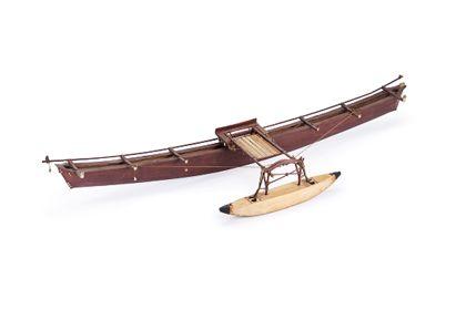 Ein sehr schlankes Auslegerboot aus rot gefärbtem Holz als mit Perlmutt und Kaurischnecken verziertes Modell.