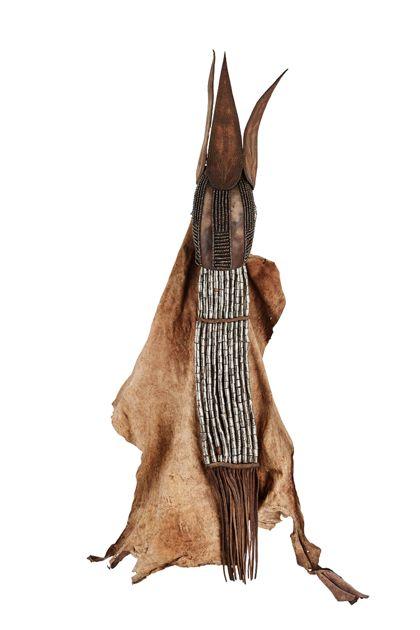 Kopfbedeckung aus Leder mit drei blattförmigen, aufgenähten Stücken. Das Kopfstück ist außen mit Eisenperlen geschmückt. Der Nackenschutz besteht aus neun Lederriemen, die der Eisenspirale als Führung dienen. Das Ganze wird von ledernen Querstücken zusammengehalten.