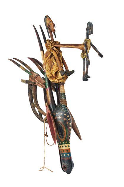 Eine hölzerne Stabpuppe in Form eines schmalen, länglichen Pferdeantilopenkopfes mit zwei an der Basis befestigten chi wara-Figuren und einer Mutter-Kind-Darstellung.