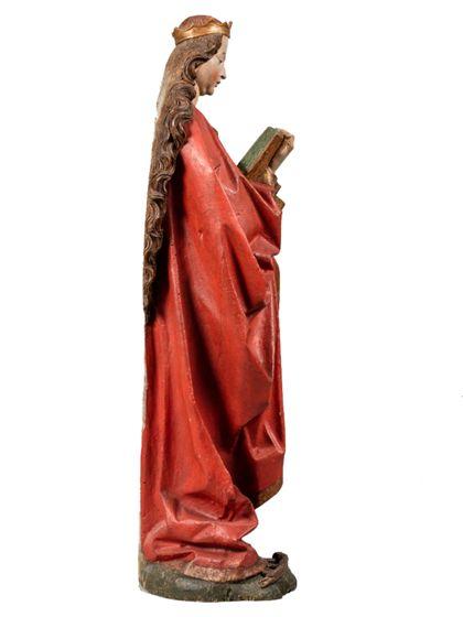 Die gefasste Holzskulptur der heiligen Katharina in langer, vorne geraffter Gewandung hält in der rechten ein Buch, in der Linken ein Schwert, Seitenansicht von links.