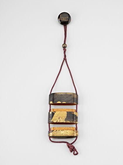 Ein kleiner, flacher Behälter aus dem Holz der japanischen Zypresse mit goldenem Lackdekor auf schwarzem Grund, der aus fünf dicht schließenden Fächern zusammengesetzt ist. Das Behältnis ziert die Darstellung zweier vom Feld kommenden Frauen, die sich mit Körben vor Sturm und Regen schützen.