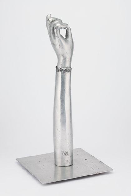 Ausgestreckter Arm mit halb geschlossener Hand aus poliertem Aluminium, auf einer Platte stehend