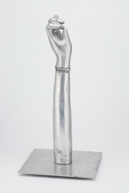 Ausgestreckter Arm mit halb geschlossener Hand aus poliertem Aluminium, auf einer Platte stehend, Seitenansicht