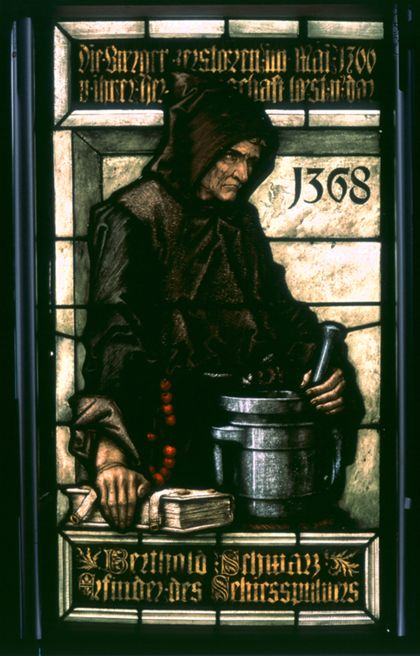 Glasmalerei, die den Franziskanermönch Berthold Schwarz bei der Herstellung von Schießpulver zeigt. Die Jahreszahl 1368 befindet sich rechts neben dem Mönch. Mit seiner rechten Hand stützt er sich auf ein Buch, während seine linke Hand in einem Pot rührt.