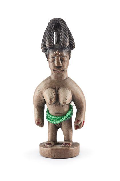 Weibliche Zwillingsfigur mit auffälliger Kronenfrisur. Die Finger und Zehen sind rot lackiert. Um den Bauch trägt die Figur eine dreifach darum gewickelte grüne Perlenkette. Die Figur steht auf einem runden Sockel.