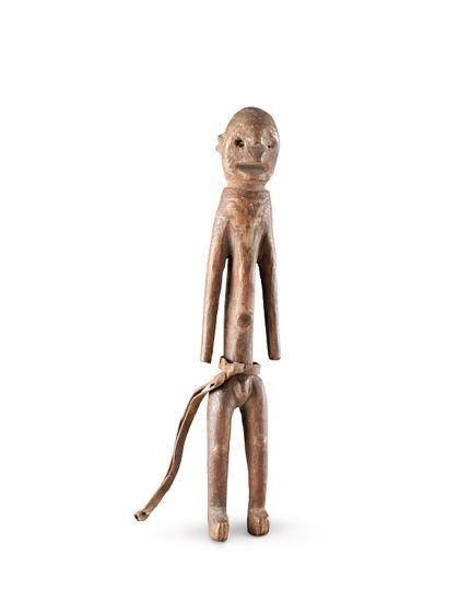 Holzfigur, die einen stehenden Mann darstellt. Stellenweise ist die Figur rot bemalt. Um die Hüften ein Lederstreifen, der seitlich herunterhängt.