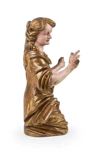 Seitenansicht von links: Der Engel kniet und hat den Blick gesenkt. Sein Gewand ist vergoldet und virtuos drapiert.