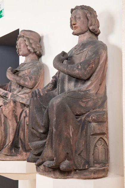 Sitzender Graf mit Stirnreif aus Sandstein, Seitenansicht von rechts.